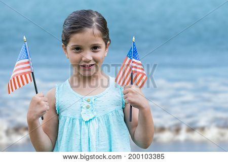 Digital composite of Girl holding USA flags in the beach