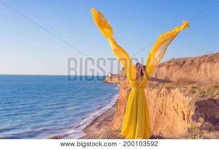 A girl in a yellow dress on a seashore