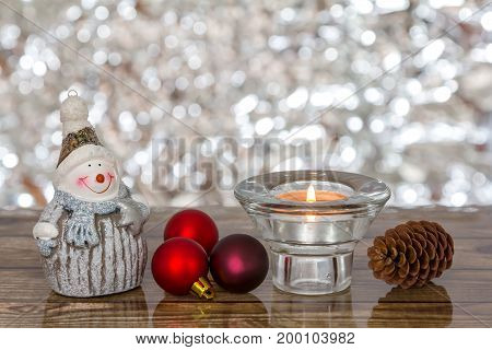 nowman and Christmas decorations on wooden background. Space for text.