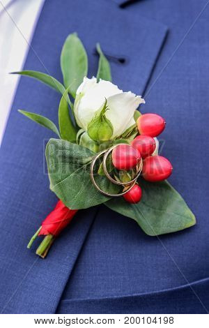 wedding rings on boutonniere on jacket of groom