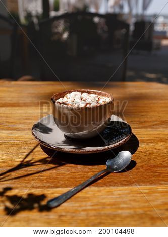 A close-up of a gray porcelain mug of sugar cappuccino with marshmallows. Sweet coffee drink on wooden table background. A cup with a round plate and a metal spoon. Copy space. Relaxation concept.