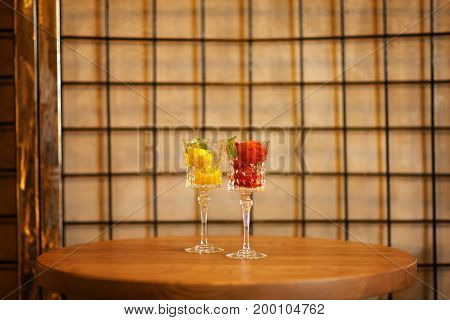 Close-up picture of two portions of bright berry ice cream in crystal glasses. Refreshing sorbet scoops on a light latticed background. Summer desserts with decorative mint leaves. Copy space.