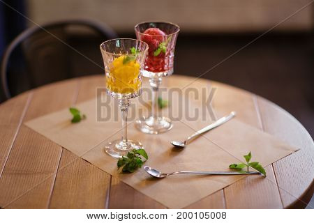 Summer desserts with decorative mint leaves. Close-up picture of two portions of bright berry ice cream in crystal glasses. Refreshing sorbet scoops on a light latticed background. Copy space.