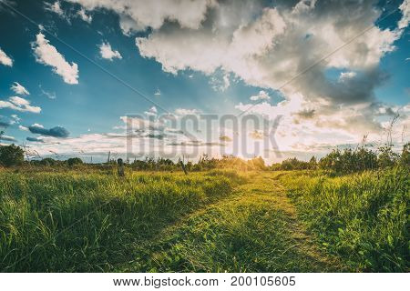 Beautiful Sunset, Sunrise Over Rural Meadow. Dramatic Sky And Country Road Path Way Lane. Countryside Landscape At Sunset Dawn Sunrise. Skyline.
