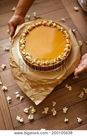 Top view of a woman's hands with round cake from condensed milk, honey and a shortbread decorated with sweet popcorn on a paper stand and on a blurred wooden background. Sweet dessert with popcorn.