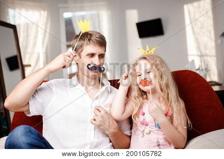 Joyful father and daughter with paper crowns and mustaches while sitting togheter on red chair at home