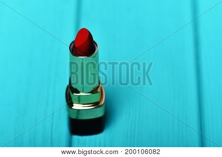 Red Lipstick On Blue Wooden Background