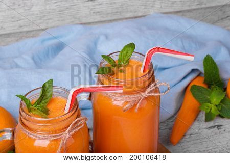 Closeup of a table with a blue napkin, wholesome carrots full of vitamins, sappy green leaves of mint and two mason jars with refreshing carrot smoothie and basil on a light blurred background.