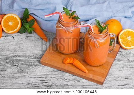 A table with green leaves of mint, sappy oranges, a wooden board with slices of carrot two mason jars of carrot smoothie with basil on a light background.
