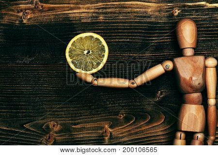 wooden puppet holding colorful fresh yellow lemon slice on brown vintage background top view