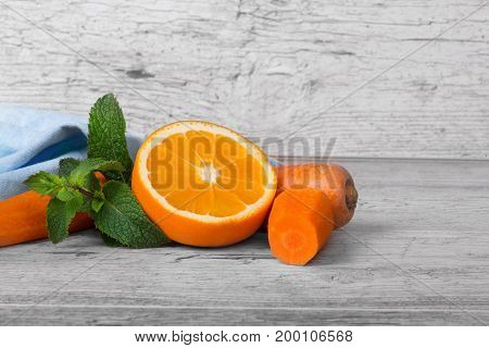 Wholesome full of vitamins carrots, juicy half of orange and succulent green leaves of mint on a light wooden background.