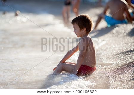 Cute Boy Playing On The Beach In The Water