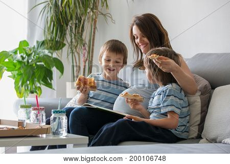 Happy young family pregnant mother and two boys eating tasty pizza at home sitting on the sofa reading a book and having a laugh