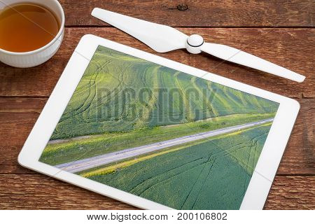 green soybean fields with tractor footprints in Missouri - examining drone aerial pictures of crop on a digital tablet