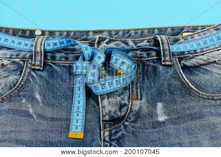 Top part of denim trousers isolated on blue background. Blue jeans with blue measure tape instead of belt. Healthy lifestyle and dieting concept. Close up of jeans with measure tape around waist.