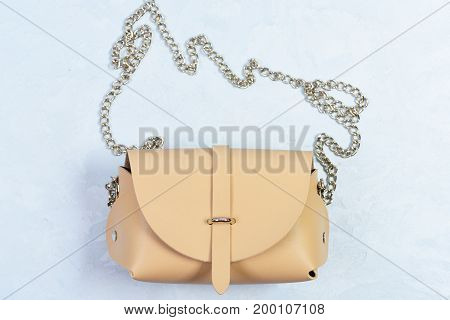 Casual Beige Leather Purse On Light Blue Background.