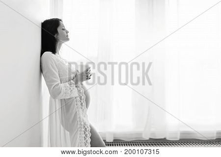 Beautiful Young Mom To Be, Leaning On A Wall, Having Her Coffee In The Morning