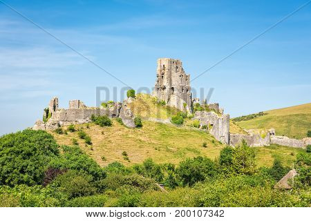 Wareham United Kingdom - June 20 2017: Ruins of Corfe Castle built by William the Conqueror in the Isle of Purbeck in Dorset viewed from the village below. Copy space in blue sky.