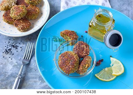 Kale bites with breadcrumbs and sesame seeds on a blue plate.
