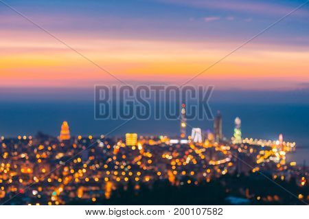 Abstract Natural Blurred Bokeh Boke Background Of Illuminated Cityscape With Skyscrapers And Modern Urban Architecture In Embankment Of Georgian Resort Town Of Batumi, Adjara Georgia.