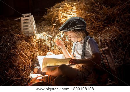 Sweet Child, Boy, Reading A Book On The Attic On A House, Sitting On A Hay Of Straw