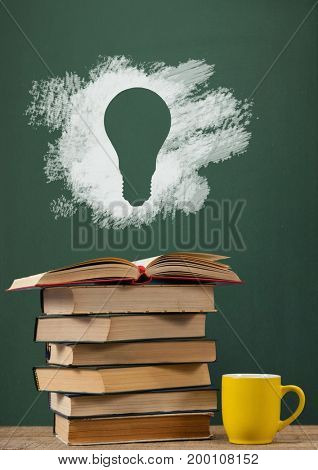 Digital composite of Books on the table against green blackboard with bulb graphic