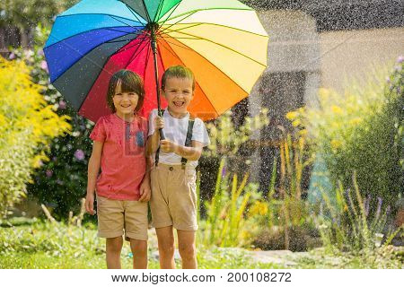 Two Adorable Children, Boy Brothers, Playing With Colorful Umbrella Under Sprinkling Water