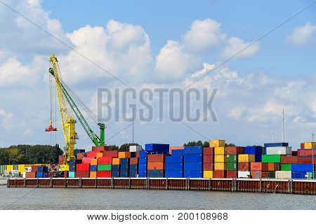 colorful shipping container and industrial crane on commercial dock along the Rhine River in Germany
