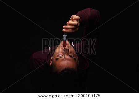 A young junkie in a purple sweatshirt is in pain because of a drug addiction, syringe with drugs. drug addiction, narcotics, drugs, suffering, concept.