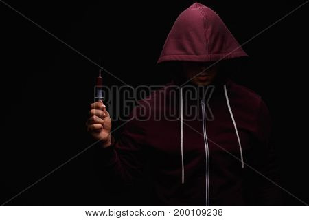 A young junkie who wears purple sweastshirt with a hood on his head is in pain because of drug addiction on a dark black background. Drug addiction, drugs, pain, concept.