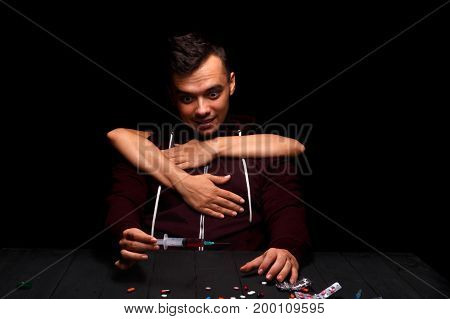 A close-up of a guy with a drug addiction on a black background. Drug-dependent with a syringe. Liquid ecstasy in a syringe. Hands keeping a boy from the drug injection. Drug concept. Copy space.