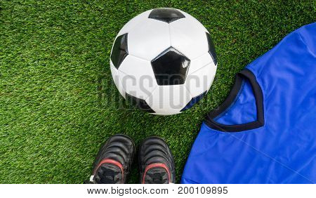 Soccer concept : Football (soccer ball) old soccer boots blue soccer kit (t-shirt) on green grass background. Flat lay with copy space.