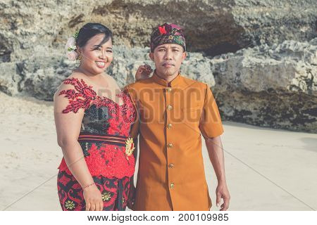 Lovely Honeymoon Balinese Couple In Traditional Clothes Together On The Beach Dreamland. Bali Island