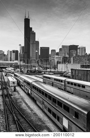 Chicago - March 2017, IL, USA: Chicago skyline at cloudy day. Railroad tracks with train office buildings in downtown and the Willis (Sears) Tower.