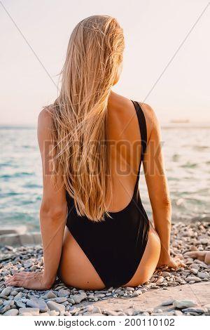 Beautiful young woman in bikini swimwear sit on beach and sea with warm sunset colors.