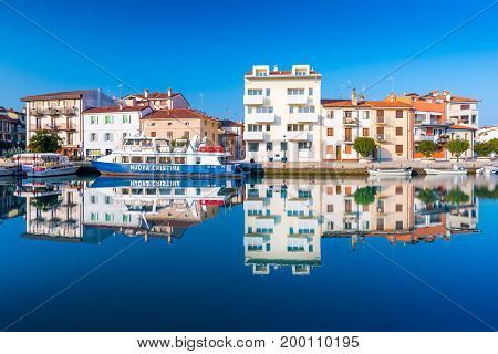 Grado - December 2015, Italy: Colored residential houses mirror reflected in canal with water.