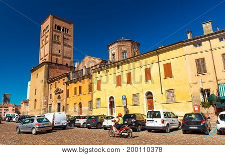Mantua (Mantova) - July 2017, Lombardy (Lombardia) region, Italy: View of the street with traffic old historical buildings and Mantua Cathedral with bell tower