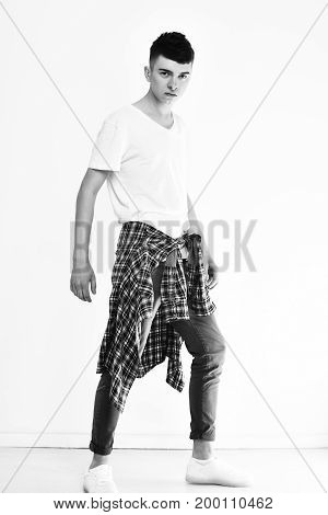 handsome stylish man young caucasian guy with serious face in fashionable grey pants tshirt and checkered shirt isolated on white background