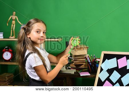 Girl Shows Time On Green Clock With Her Pencil