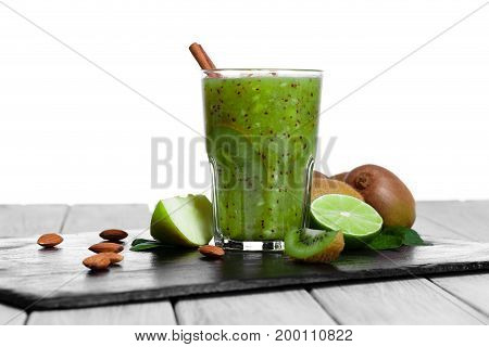 A colorful set of organic products on a black plate on a gray wooden table. Refreshing kiwi and lime juice isolated over the white background. Homemade desserts with exotic citrus fruits.