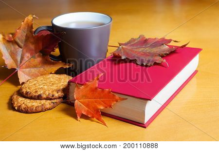 Tea with cookies book and autumn leaves. Selective focus