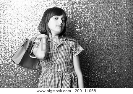 small pretty girl or cute fashionable child with long brunette hair and adorable smiling happy face in checkered dress with female red leather bag on metallic silver background copy space