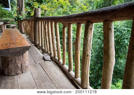 Wooden balcony in forest.Wooden balcony with rain forest as background. For dining with family atmosphere at Tree House hideaway, Mae Me, Chiang Mai, Thailand.