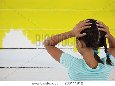 Digital composite of Girl looking at painted yellow wall