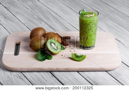 Kiwi fruits full of nutritious vitamins, cinnamon sticks and walnuts on a wooden desk and on a gray table background. A glass full of smoothie from juicy kiwi, grated nuts, and mint on a cutting board.