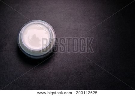 moisturizer cosmetic cream swirl at glass pot, on white wood table directly above