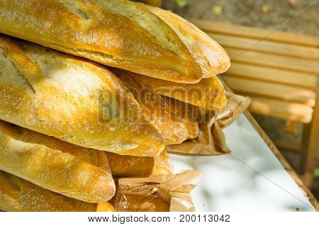 Pile of freshly baked rustic French baguettes on garden table wooden chair outdoor picnic preparation. Summer sunlight flecks lifestyle.
