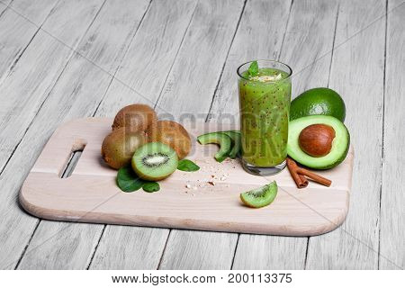 A colorful composition of organic, rustic fruits and vegetables on a cutting desk. A blended kiwi cocktail with peppermint and cinnamon. Cut avocados and heap of kiwis on a wooden background.