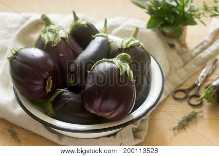Aubergines In A Bowl On A Wooden Table. Vertical. Selective Focus.
