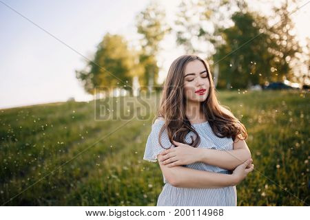 pregnant girl in a light dress is standing and hugging her belly with fat. Concept maternity, pregnancy, childbirth. Sunset